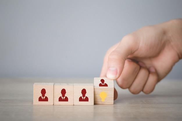 Ręka przerzuca kostkę z ikoną żarówki i ludzki symbol.