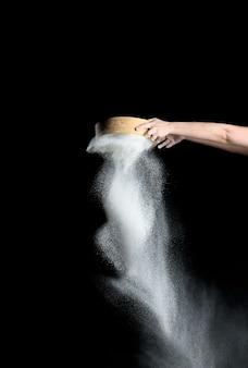 Ręka przesiewa białą mąkę pszenną przez okrągłe drewniane sito na czarnym tle, wylewa się produkt