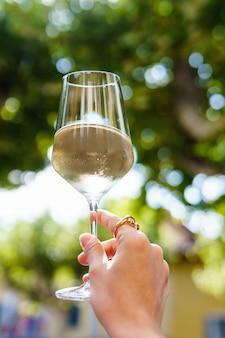 Ręka przy lampce białego wina