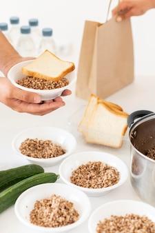 Ręka przygotowująca porcje jedzenia na darowiznę