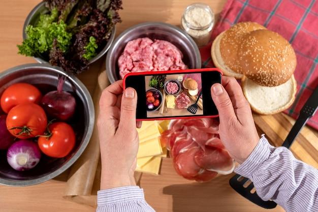 Ręka robi zdjęcie telefonem produktów i składników do gotowania na stole big burgera lub cheeseburgera