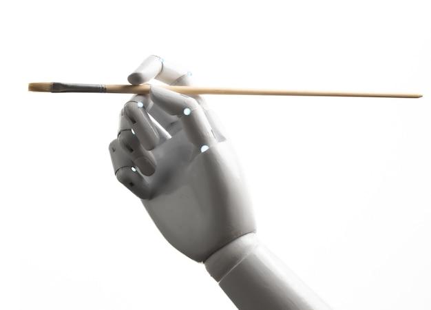 Ręka robota trzyma pędzel na białym tle