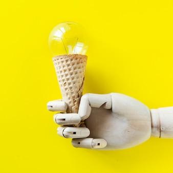 Ręka robota trzymająca lody z żarówką