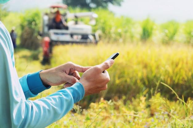 Ręka rolnika za pomocą telefonu komórkowego. rolnictwo