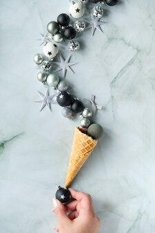 Ręka równoważy rożek do lodów na czarnej bombce