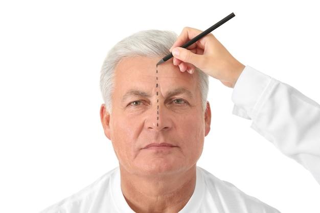 Ręka rysująca linię korekcyjną na twarzy mężczyzny na białym tle