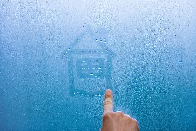 Ręka rysuje dom na szklanym oknie z tłem kropli