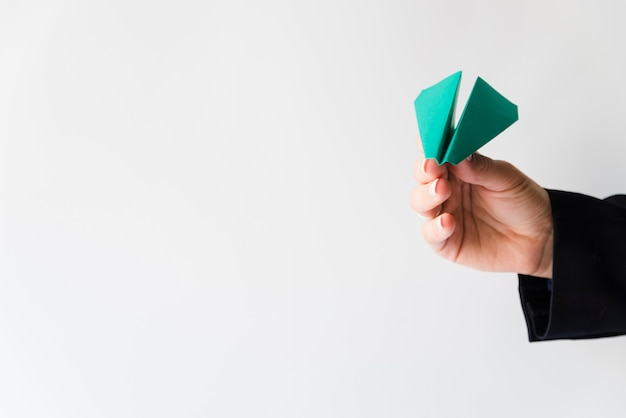 Ręka rzuca zielony papierowy samolot