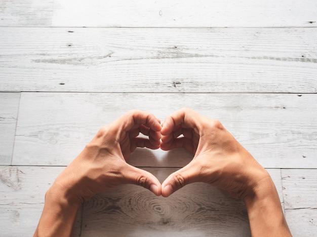 Ręka serce na tle drewna z widokiem z góry na światło słoneczne i cień przyrody, miłość i zdrowa koncepcja