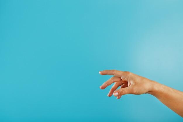 Ręka sięga po pomoc na niebieskim tle.