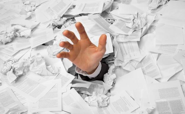 Ręka sięga z pogniecionych papierów