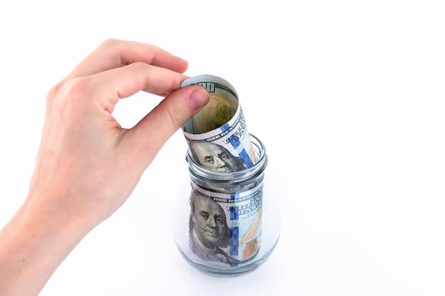 Ręka składa papierowe amerykańskie sto dolarów, pieniądze w szklanym słoju. koncepcja dokonywania wpłat, oszczędzania pieniędzy. białe tło. skopiuj miejsce.