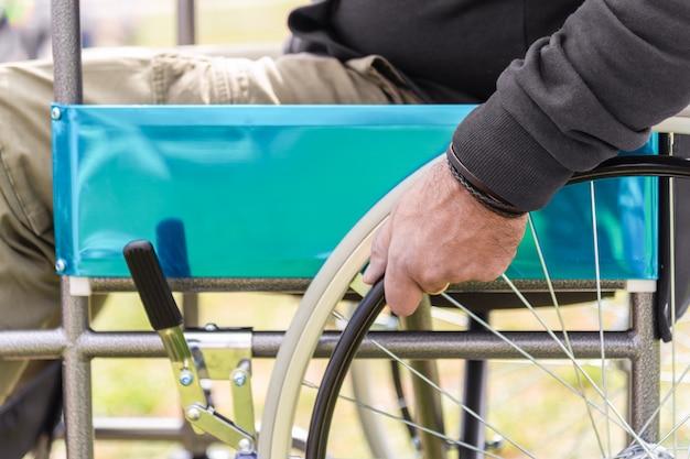 Ręka sparaliżowanego dorosłego człowieka na wózku inwalidzkim