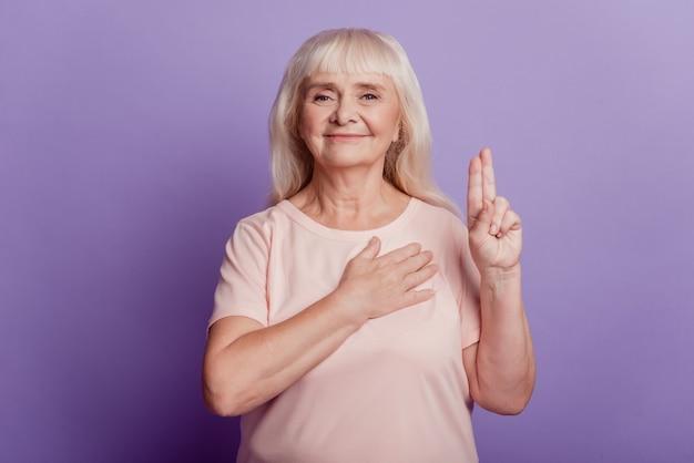 Ręka starzejącej się kobiety na sercu sprawia, że znak przysięgi na białym tle na fioletowym tle