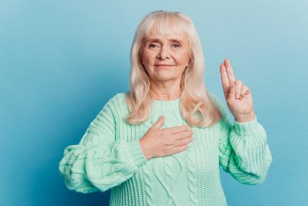 Ręka starzejącej się kobiety na sercu sprawia, że znak przysięgi na białym tle na niebieskim tle