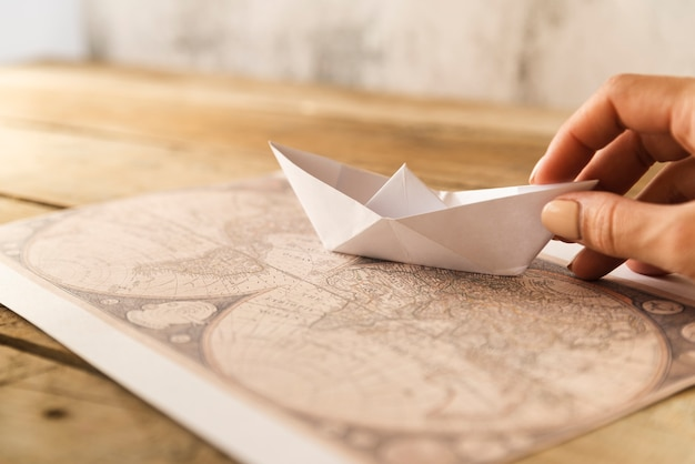 Ręka stawia papierową łódź na mapie