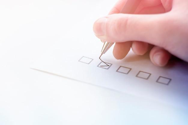Ręka stawia znacznik wyboru na papierze firmowym