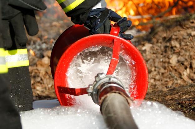 Ręka strażaka trzyma wąż strażacki, aby ugasić pożar. ugasić ogień. wąż pożarowy