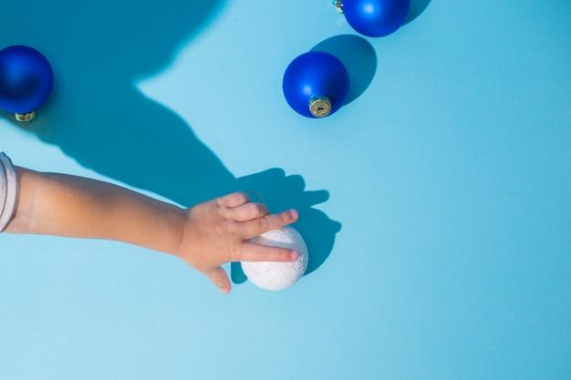 Ręka streszczenie obraz trzyma ozdoby choinkowe na niebieskim tle. płaski świeckich, widok z góry.