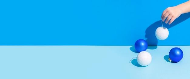 Ręka streszczenie obraz trzyma ozdoby choinkowe na niebieskim tle. transparent.