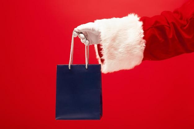 Ręka świętego mikołaja trzyma prezent na czerwonym tle. sezon, zima, wakacje, uroczystość, koncepcja prezentu