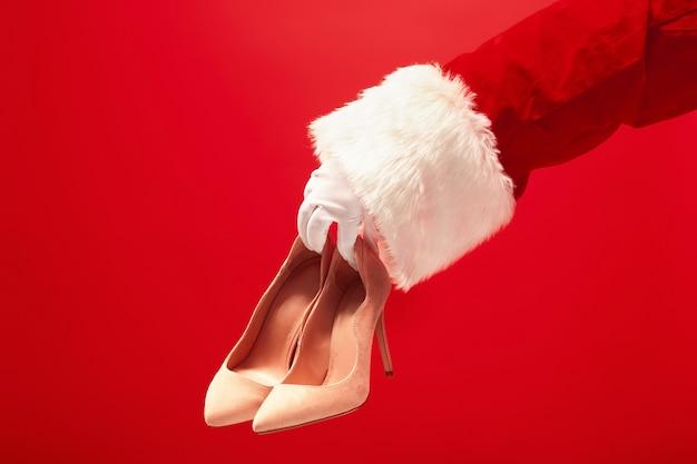 Ręka świętego mikołaja trzymając buty damskie na czerwonym tle. sezon, zima, wakacje, uroczystość, koncepcja prezentu