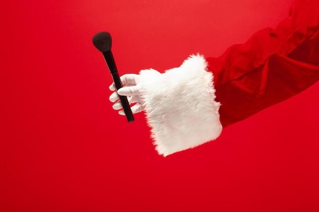 Ręka świętego mikołaja trzymająca pędzel do makijażu na proszek na czerwonym tle. sezon, zima, wakacje, uroczystość, koncepcja prezentu