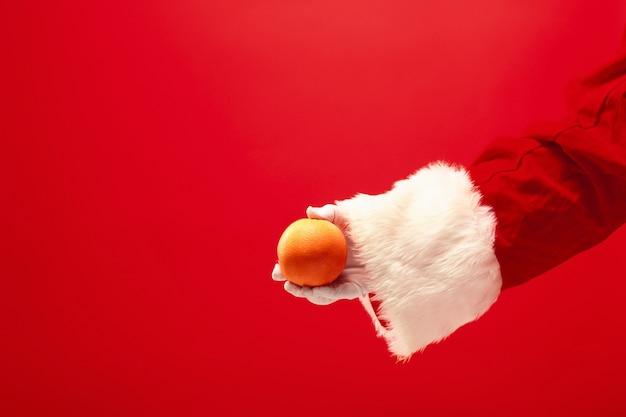 Ręka świętego mikołaja trzymająca pomarańczowy owoc na czerwonym tle. sezon, zima, wakacje, uroczystość, koncepcja prezentu