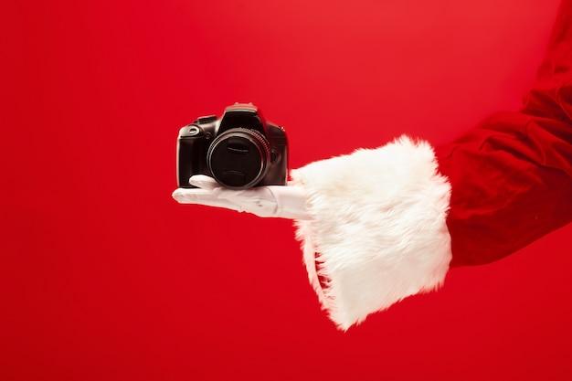 Ręka świętego mikołaja trzymającego aparat na czerwonym tle. sezon, zima, wakacje, uroczystość, koncepcja prezentu