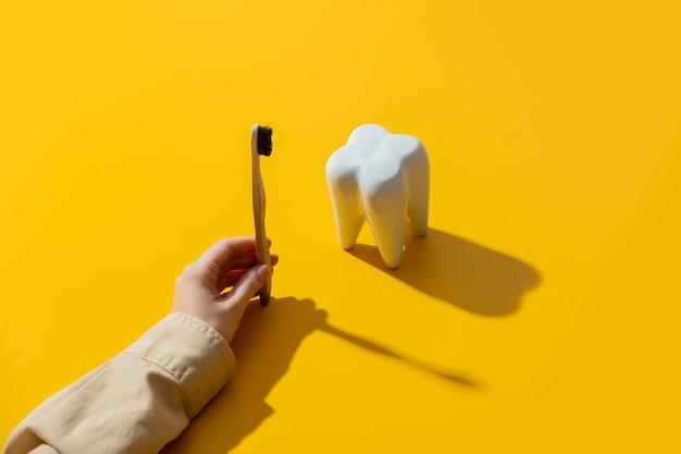 Ręka szczotkuje ząb na żółtej powierzchni