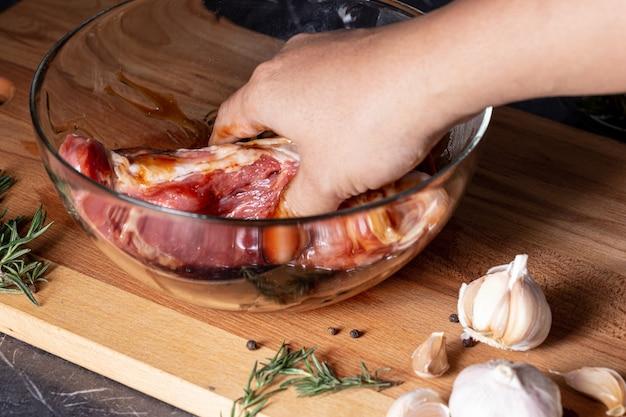 Ręka szefa kuchni marynowała świeżą wołowinę w szklanej filiżance dla stków na marmurowym stole, zbliżenie