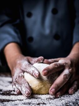 Ręka szefa kuchni wyrabiania surowego ciasta z posypywania białą mąką na kuchennym stole.