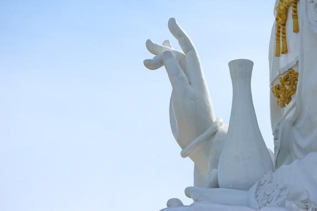 Ręka tajlandzka sławna duża biała bodhisattva guanyin statua z nieba tłem.