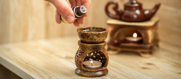 Ręka terapeuty wylewa krople olejku eterycznego do ceramicznego dyfuzora w salonie spa
