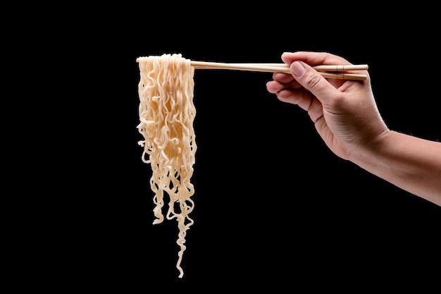 Ręka trzyma bambusowe pałeczki i widelec nad makaronem instant