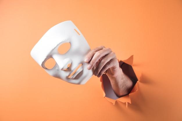 Ręka trzyma białą maskę na pomarańczowym tle