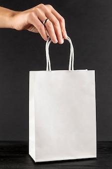 Ręka trzyma białą papierową torbę