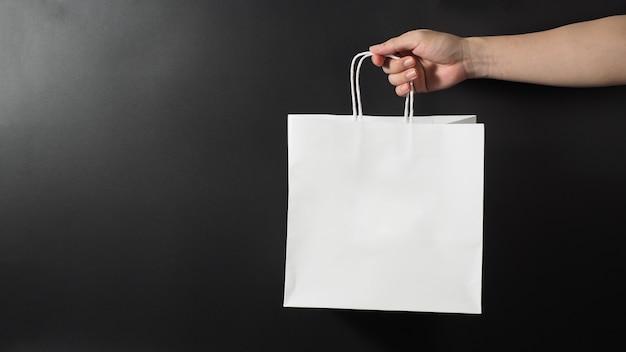 Ręka trzyma białą torbę na zakupy na białym na czarnym tle.