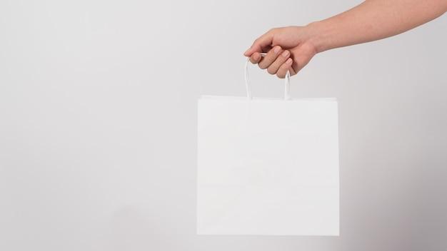 Ręka trzyma białą torbę na zakupy na białym tle.