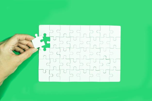 Ręka trzyma białą układanki grę na zielonym tle.