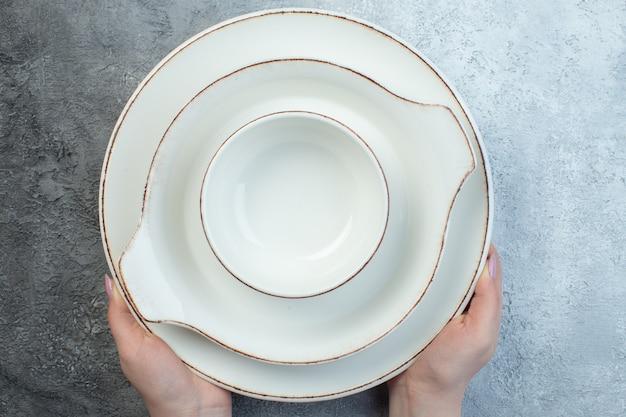Ręka trzyma białą zastawę stołową na pół ciemnej jasnoszarej powierzchni o trudnej powierzchni
