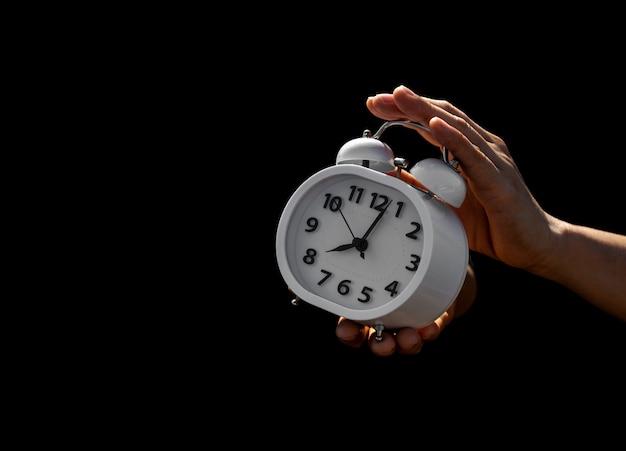 Ręka trzyma białego budzika w ciemności. myślenie i kontrola pomysłów na czas.