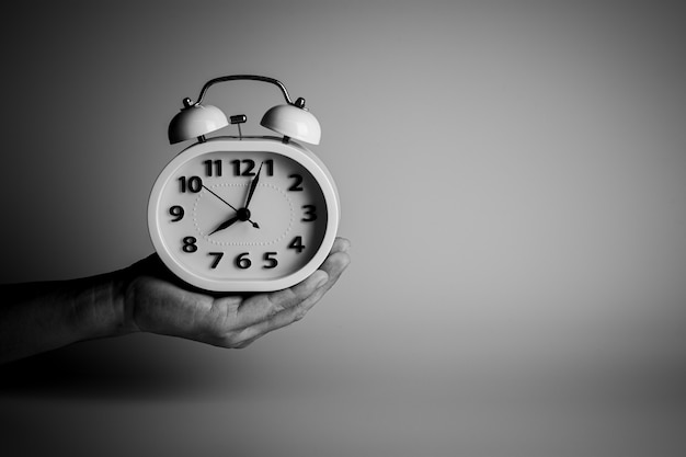 Ręka trzyma biały budzik. myślenie i kontrola pomysłów na czas.