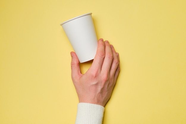 Ręka trzyma biały kartonowy kubek na żółtym tle. makieta.