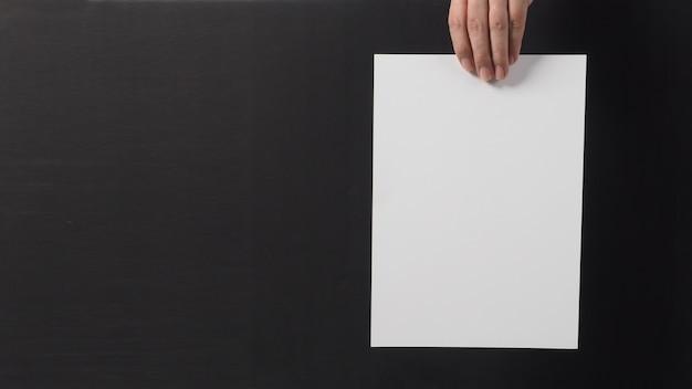 Ręka trzyma biały papier a4 na czarnym tle.