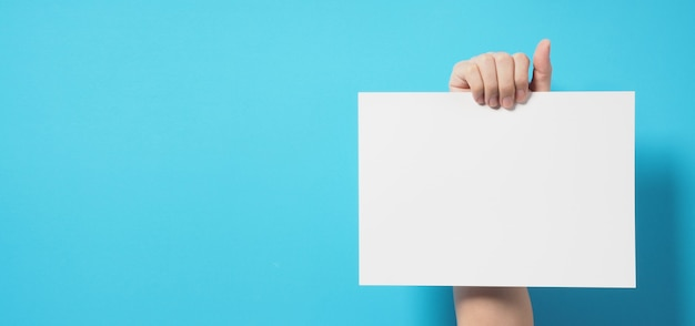 Ręka trzyma biały papier a4 na niebieskim tle.