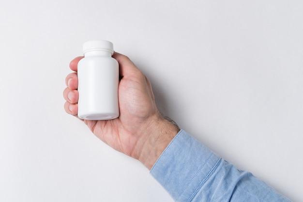 Ręka trzyma biały słoik pigułek. pojemnik farmaceutyczny, makieta na białej ścianie
