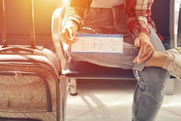 Ręka trzyma bilety lub kartę pokładową. podróż lotnicza przy bramce czeka w terminalu.