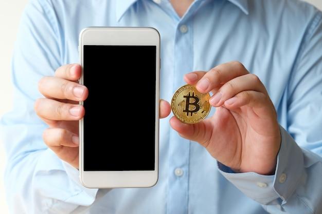 Ręka trzyma bitcoin i smartphone z pustego ekranu tłem, wyśmiewa up, cryptocurrency