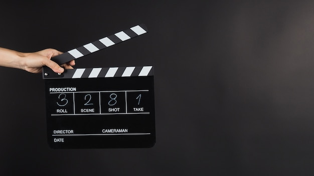 Ręka trzyma black clapperboard lub plansz filmowy z napisem w numerze. wykorzystuje się go w produkcji wideo, filmie, przemyśle kinowym na czarnym tle.